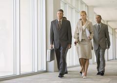 Executives walking through corridor of office building Stock Photos