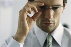 Young businessman adjusting glasses, portrait Stock Photos