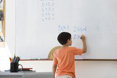 Elementary school student working math equations on whiteboard - stock photo