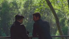 Friendly Men in Suits Talking by Railing in Natural Setting Stock Footage