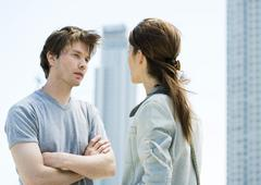 Young couple having argument in front of highrises Stock Photos