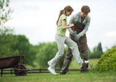 Stock Photo of Man helping girl dig in yard