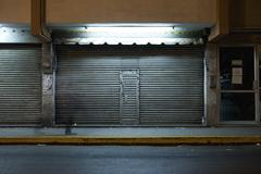 Store front with locked roll-up door at night Stock Photos