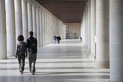 Tourists walking thorugh the Stoa of Attalos in the Ancient Agora, Athens, - stock photo