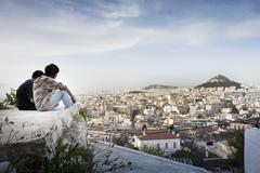 Tourists sitting on rock overlooking Athens, Greece and Mount Lycabettus - stock photo