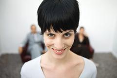 Woman smiling at camera, one eyebrow raised, close-up - stock photo