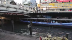 ASIA TRANSPORTATION (BOATS) - Canal level view w/ boats, overpass, pedestrians Stock Footage