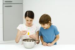 Two young siblings cooking together, girl cracking egg, both looking down - stock photo