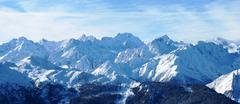 winter alpine mountain scene under a blue sky - stock photo