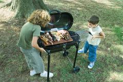 Two boys standing next to tray of grilled meat on barbecue Stock Photos