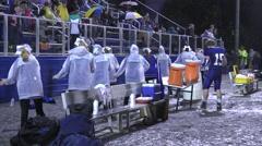 Cheerleaders in rain gear cheering on mud soaked night Stock Footage