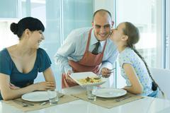 Man serving wife and daughter spaghetti, girl kissing father on cheek - stock photo