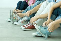 Four teen friends tying laces, all wearing canvas shoes Stock Photos