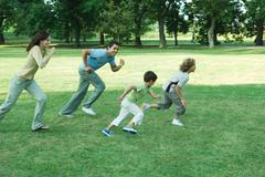 Family outdoors, running across grass together Stock Photos