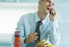 Man eating junk food and using cell phone Stock Photos