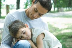 Boy and father, boy sleeping in man's lap - stock photo