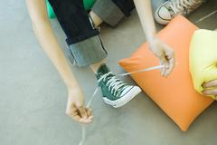Teenager tying laces of canvas shoe, partial high angle view Stock Photos