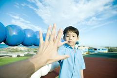 Boy on playground, holding out hand to adult hand Stock Photos