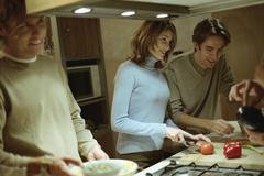 Friends preparing food in kitchen Stock Photos