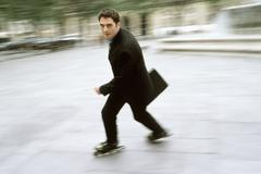 Man in business attire inline skating carrying briefcase in city square Stock Photos