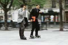 Stock Photo of Men in business attire rollerskating together along sidewalk, one phoning, the