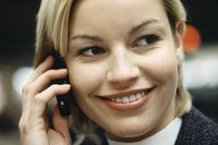 Woman phoning using cell phone smiling, glancing sideways, portrait - stock photo