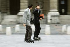 Stock Photo of Men in business attire inline skating together along sidewalk, one phoning
