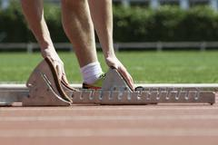 Runner bending over to adjust starting blocks, cropped Stock Photos