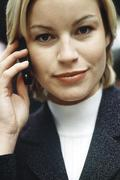 Stock Photo of Woman phoning using cell phone looking with optimistic determination at camera,