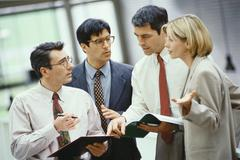 Four business colleagues standing discussing document and agenda Stock Photos