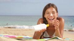 Sunscreen woman applying suntan lotion on beach Stock Footage