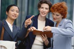 Three businesswoman looking at agenda, one pointing out of frame Stock Photos