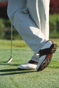 Golfer standing with ankles crossed, knee down - stock photo