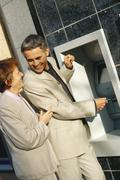 Mature couple standing at ATM machine Stock Photos