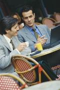 Two businessmen sitting at sidewalk cafe, using laptop Stock Photos
