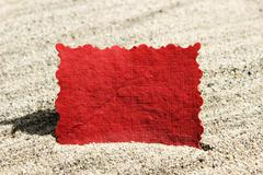 blank red message note card in sand - stock illustration