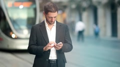 Texting on iphone downtown [slider shot and lens flare] Stock Footage