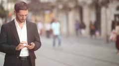 Man texting on Iphone in a urban environment [lens flare] - stock footage