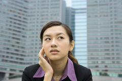 Businesswoman holding head and looking away, high rises in background - stock photo