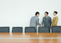 Business associates shaking hands in conference room - stock photo