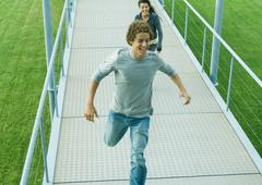 Teenage couple running on walkway - stock photo