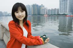 Young woman standing by river, high rises in background - stock photo