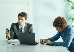 Businessman and intern sitting at table - stock photo
