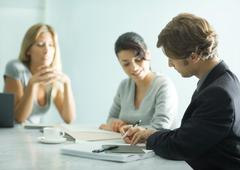 Mature man sitting at table with teenage girl and young female professional, - stock photo