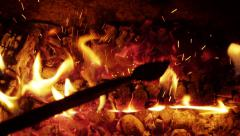 Poking the fireplace in the evening - stock footage