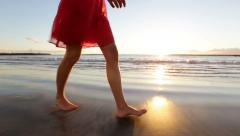 Woman feet and legs walking on beach at sunset Stock Footage