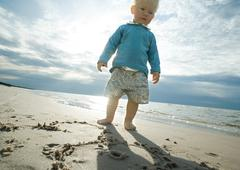 Toddler standing on beach, low angle view - stock photo