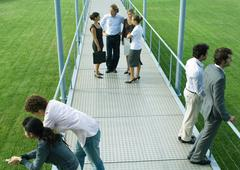 People standing in small groups on walkway, high angle view Stock Photos