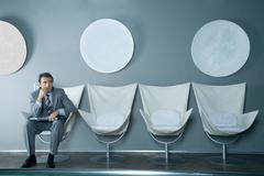 Businessman sitting at end of row of chairs, holding laptop on lap Stock Photos