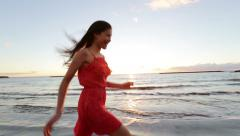 Happy woman running on beach in summer dress on vacation Stock Footage